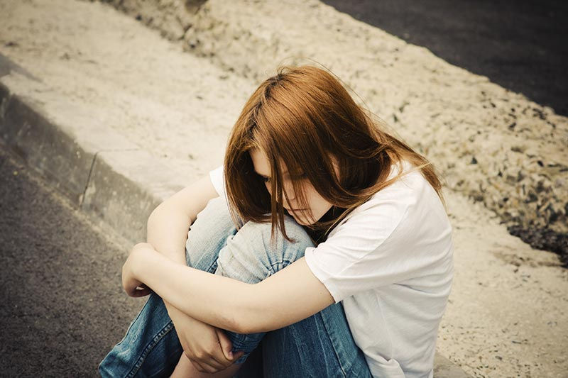 Picture of a teenage girl sitting hugging her knees